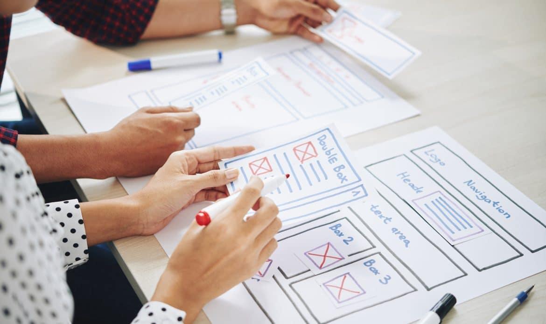 Equipo de diseñadores de UI conversando ideas para la interfaz del sitio web